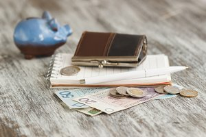 Polish zloty with little wallets and piggy bank on the wooden background