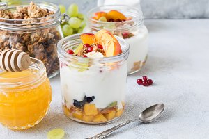 Healthy breakfast table: yogurt, fruits, honey, muesli and granola