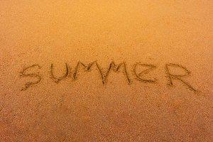 Text summer on beach sand