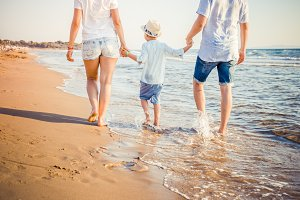 Back view of young blonde family walking on beach