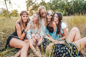 Six girls in nature are sitting on the grass.