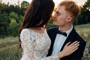 Happy newlyweds kissing at sunset