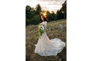 young bride outside on a summer meadow at the sunset