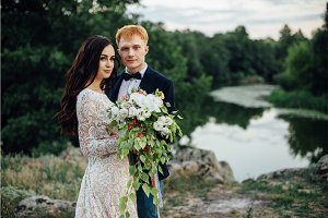 Portrait of a happy newlywed couple on the river bank
