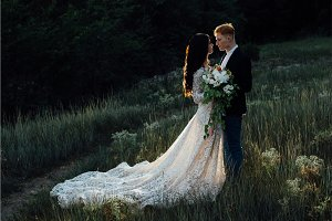 Newlyweds standing and hugging outdoors