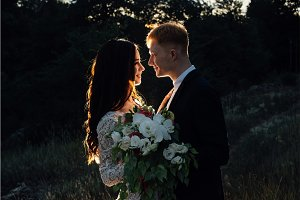 Newlyweds standing and hugging outdoors, close-up