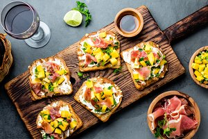 Toasts with cream cheese, ham jamon serrano and mango served on wooden board with red wine, gray slate background, top view