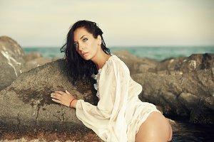 beautiful girl in sea water near the rocks