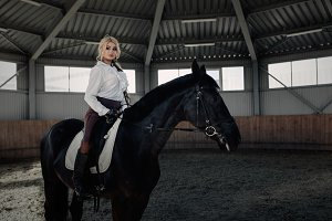 Beautiful elegant young blonde girl sits on a her black horse dressing uniform competition white blouse shirt and brown pants.