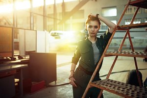 Portrait of modern young woman working in engineering standing by jet plane near the stairs looking at camera