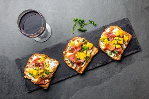 Toasts with cream cheese, ham jamon serrano and mango served on black slate board with red wine, top view, gray slate background