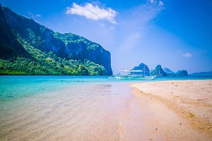 Traditional banca boat anchored at sandy beach with pure crystal clear water. El Nido, Philippines
