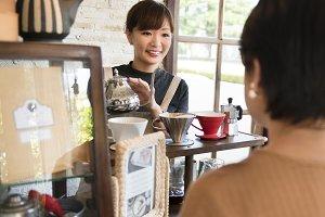 Cheerful barista at coffee shop