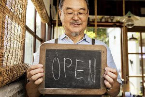 Man holding open sign in shop