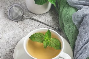 Natural mint tea and fresh mint leaves on a gray background