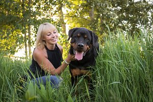 Girl with Rottweiler in Tall Grass