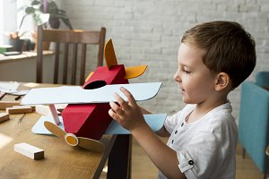 Boy playing toy plane