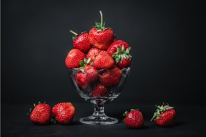 Ripe juicy strawberries in a glass on a dark background