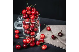 ripe juicy cherries in a glass on a dark background