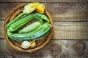 Fresh zucchini on wicker mat on dark wooden background