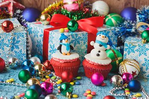 Christmas cupcakes with colored decorative snowman and penguin made from confectionery mastic