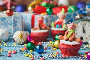 Christmas cupcakes with colored decorative deers made from confectionery mastic
