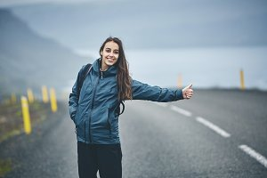 a woman tourist on the empty road on the fjord in Iceland