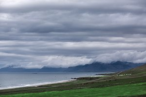 the austere Icelandic landscape with field in the foreground and the mountains and the fjords in the background