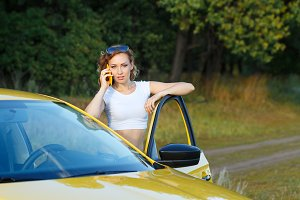 Girl is talking on phone by car