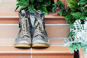 Old worn boots at doorstep