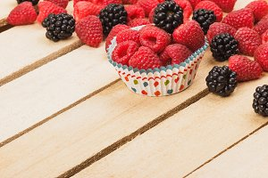Red raspberries and blackberry on the light wooden background