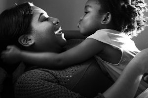 Cheerful black mother and daughter