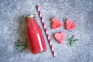 Watermelon rosemary smoothies in a bottle on a gray background