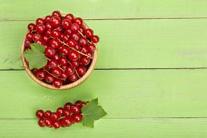 Red currant berries in a wooden bowl with leaf on the green wooden background with copy space for your text. Top view