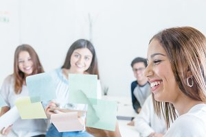 Smiling woman with colleagues in office room
