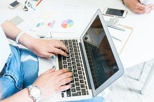 Crop woman using laptop