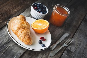 Continental breakfast with croissant, jam and fruits