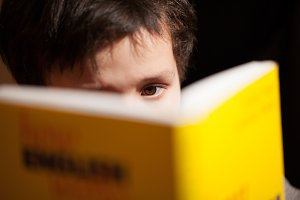 Young boy concentrating on reading a