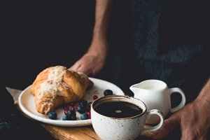 Hands holding wooden tray with continental breakfast croissant, coffee, cream and fruits