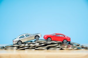 car model on stack of coins