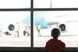 Boy looks at the plane at the airpor