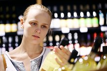 Woman shopping for alcohol in a bott