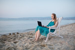 Woman talking skype at the beach