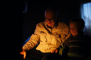 Grandfather and grandson near fire a
