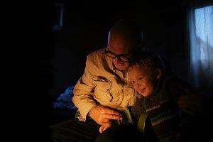 Grandfather hugs his grandson near f