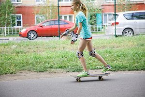 Teenager girl learning to ride on skateboard