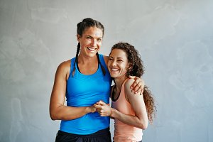 Smiling friends high fiving each other while exercising together