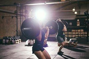 Sportive people doing knee bends with barbells