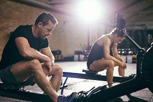 Two people taking break on rowing machine