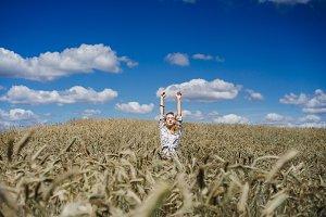 The girl is having fun in the wheat